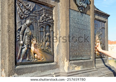 Detail of the statue of St. John of Nepomuk on Charles bridge in Prague - the oldest one on the bridge. Touching it brings good fortune and ensures returning to the city of Prague.  - stock photo