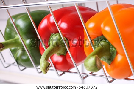 detail of three bell pepper in a chrome cage