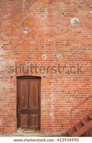 Detail of Timber door in red brick building and metal firte escape