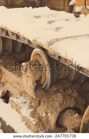 Detail of tractor track in construction site with dust and snow - aged photo effect, vintage retro - stock photo
