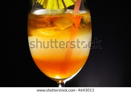 Detail of triple layered drink with spiral lemon slice, umbrella and straw in studio light - stock photo