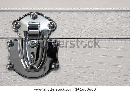 Detail of trunk lock in metal and leather - stock photo