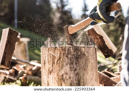 Detail of two flying pieces of wood on log with sawdust. Man is chopping wood with vintage axe. Frozen moment. - stock photo