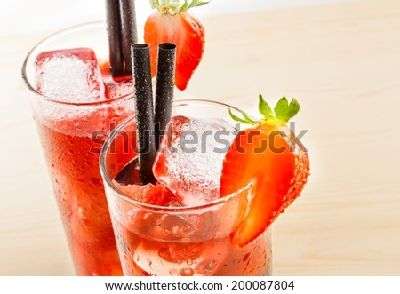 detail of two glasses of strawberry cocktail with ice on light wood table and a white background - stock photo
