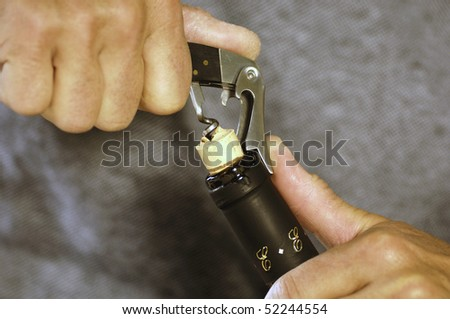 detail of two hands broaching a bottle of wine - stock photo