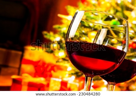 detail of two red wine glasses against christmas tree background, christmas atmosphere - stock photo