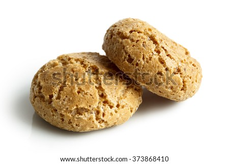 Detail of two whole Italian amaretti biscuits isolated on white in perspective.