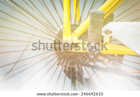 Detail of used grungy bicycle: back wheel with spokes and chain. Old dirty bike with worn yellow and white metal parts. Popular and moderate means of transport. Sport and activity. - stock photo