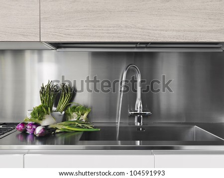 detail of vegetables near to steel faucet in a modern kitchen