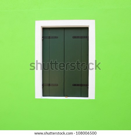 detail of vivid green facade with window with closed shutters, Burano, Venice, Italy, Europe - stock photo