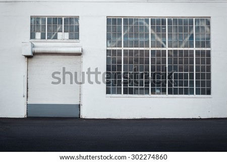 Detail of warehouse building with white walls, rolling door and large window taken straight from the front - stock photo