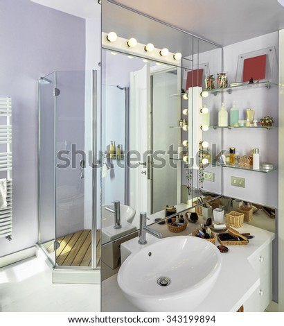 detail of washbasin in the modern bathroom with shower reflected by the large mirror over the sink - stock photo
