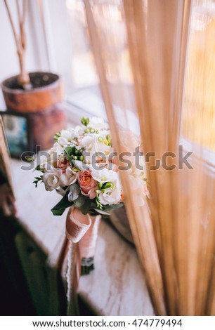 Detail of wedding bouquet standing near the window and old clock.