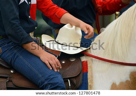 Detail of Western horse rider with a cigarette in her hand - stock photo