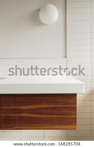 Detail of white bathroom counter and tile in a home. Wood detail under the counter.  - stock photo