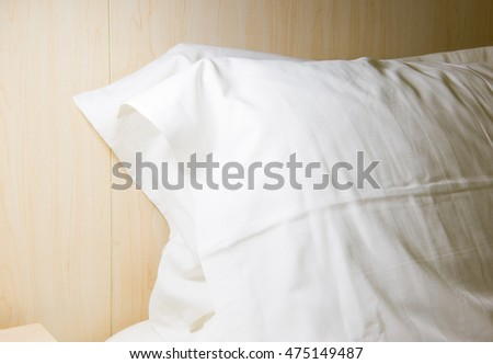 detail of white pillows sitting on a bed.