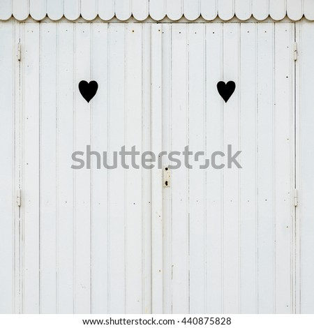 Detail of white wooden beach hut with two carved hearts in the doors. - stock photo