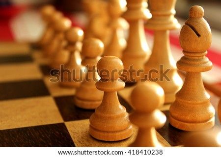 Detail of white wooden chess pieces on a chessboard. Pawn and bishop in focus  - stock photo