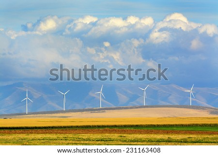Detail of windmills on wind-farm wind farm with mountains and clouds - stock photo