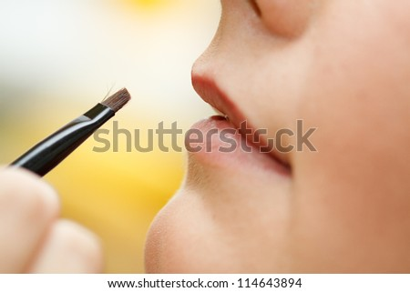 Detail of woman applying makeup using a lip brush. - stock photo