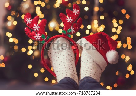 Detail of woman's feet wearing warm winter socks, small antlers and Santa's hat, placed on the table with Christmas tree and Christmas lights in the background. Selective focus on the antlers