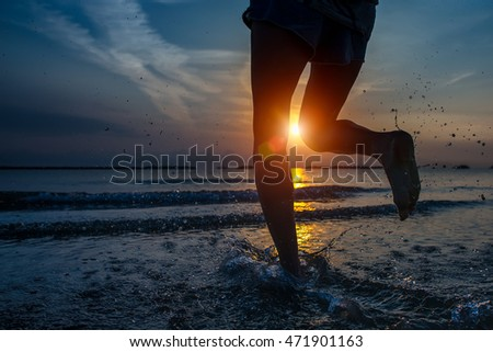 Detail of woman's legs running by the sea in a late summer dawn
