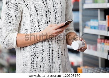 Detail of woman scanning bottle with cell phone in pharmacy - stock photo
