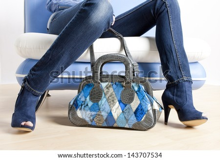 detail of woman wearing blue shoes and with handbag - stock photo