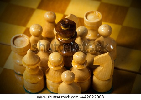 Detail of wooden black chess king, surrounded by white pieces, pawns, tower, queen, horse, bishop, on a wooden chess board - stock photo