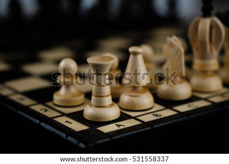 detail of wooden chess pieces on a chess board