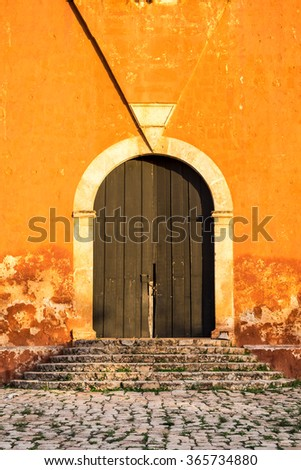 Detail of wooden door in bright orange textured wall and stone stairs - stock photo