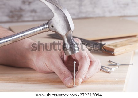 detail of worker with a nail and a hammer - stock photo
