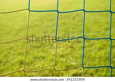 Detail of yellow blue crossed soccer nets, soccer football in goal net with grass on outdoor playground in the background. - stock photo