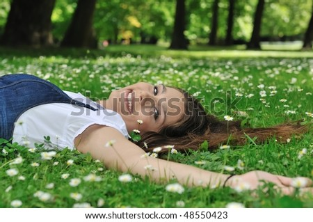 Detail of young woman lying in fresh green grass with flowers - above view