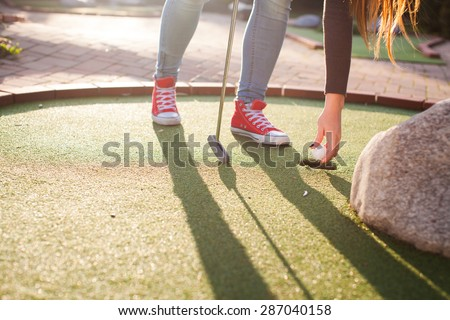 Detail of young woman playing mini/adventure golf on a beautiful sunny summer day (colorful image, photo was taken in warm evening light)