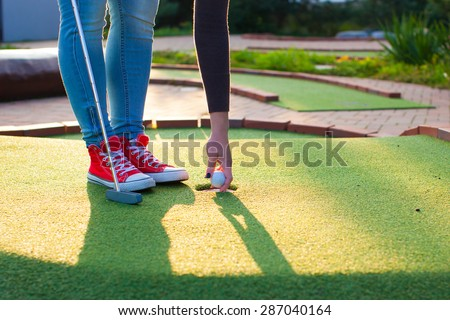Detail of young woman playing mini/adventure golf on a beautiful sunny summer day (colorful image, photo was taken in warm evening light) - stock photo