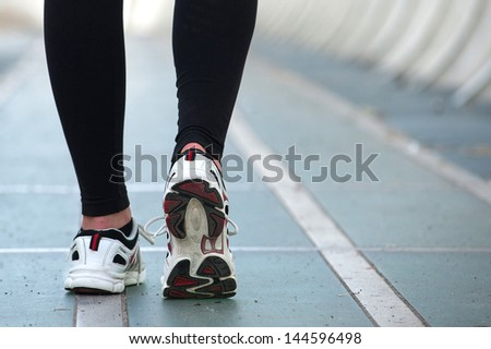 Detail of young woman runner shoes from the back. - stock photo