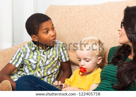 Detail of young woman speaking with children on sofa. - stock photo