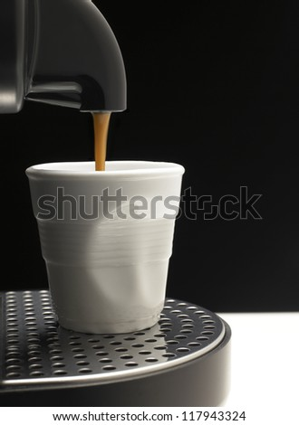 Detail on black background a coffee machine with fake cup - stock photo