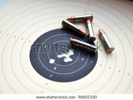 Detail on holes in target and ammunition - stock photo