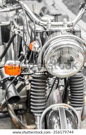 Detail on the headlight of a classic motorcycle. Big bike with harsh suspensions and yellow headlight composed of  metallic  parts.