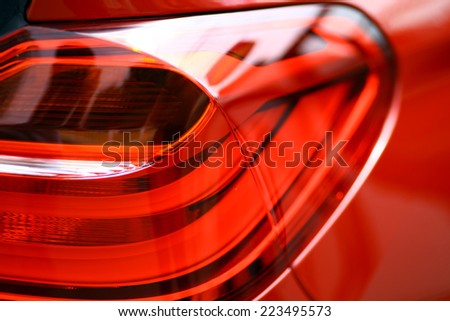 Detail on the rear light of a red car.