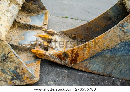 Detail os rusty excavator arms resting on concrete of construction site - stock photo