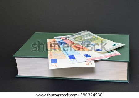 Detail photo of book with euro banknotes money on black background. Money on book with rules. Spending money on book. - stock photo