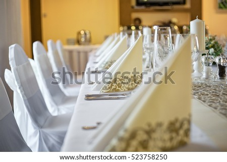 Detail photo of wedding table with focus on decorative paper napkins in beige, golden color. Table setting with empty wine and champagne glasses. Taken in hotel restaurant before wedding reception