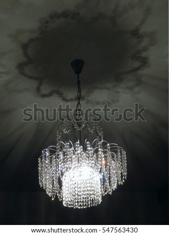 detail photography of lighting crystal chandelier and shadows on the wall