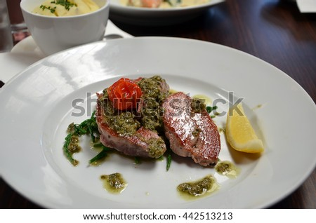 detail photography of tuna fish with capers and lemon in restaurant