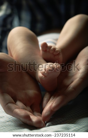 Detail picture of the baby's feet in mother's hands