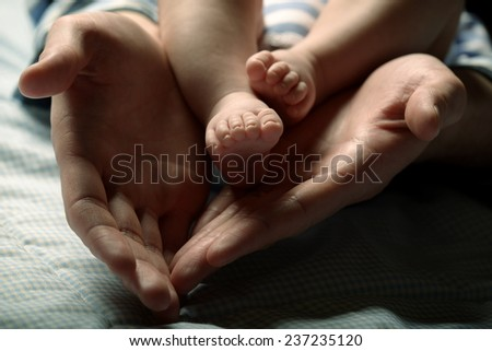 Detail picture of the baby's feet in mother's hands - stock photo