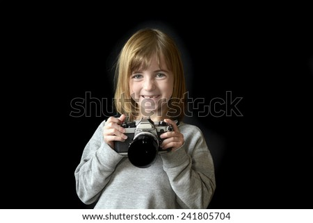 Detail portrait of young girl photographer holding old camera shooting photographs - stock photo